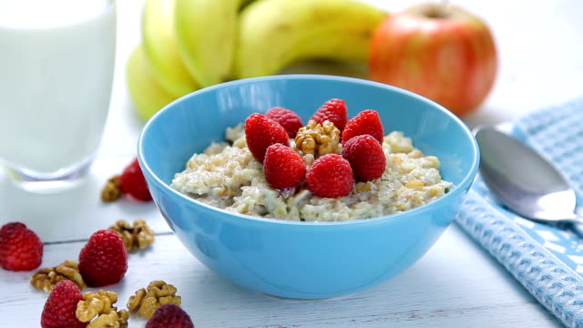 healthy breakfast - oatmeal with fresh, ripe raspberries and walnuts in a bowl standing on a wooden table video