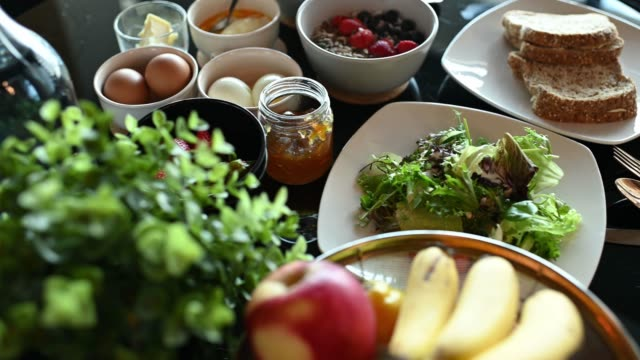 フルーツオレンジ、イチゴ、野菜、バナナ、卵、トーストパン、ヨーグルトリンゴ、ジャムをダイニングテーブルに添えた健康的な朝食 - ベジタリアン料理点の映像素材/bロール