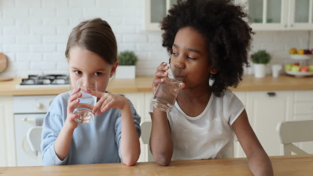 Healthy cute mixed race kids girls drinking water at home