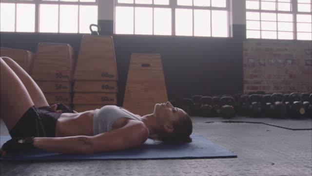 vídeos y material grabado en eventos de stock de atleta femenina sana tomando un descanso del entrenamiento de fitness - acostado