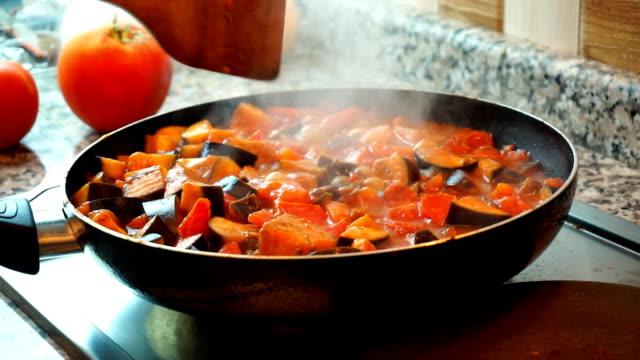cibo sano stile di vita: bellissima donna cucina informale, mescolare verdure in padella cuocere a fuoco lento in cucina. primo piano, statica, rallentatore 60 fps. - melanzane video stock e b–roll