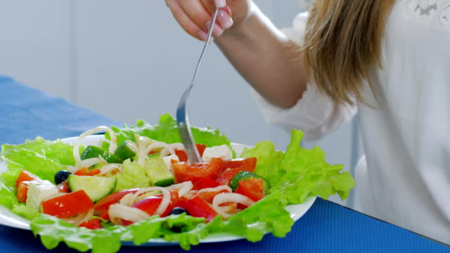 healthy food, plate of green salad close-up that is eating women at table video