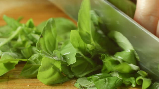 healthy fresh green basil food prep cutting up in kitchen - friskhet bildbanksvideor och videomaterial från bakom kulisserna
