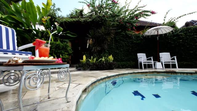 バリ島のプール付きスパ リゾートのテーブルで飲んで健康的なフルーツ - ヴィラ点の映像素材/bロール