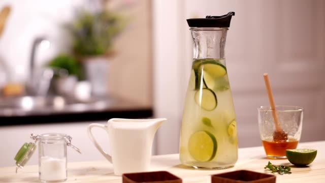 vídeos de stock e filmes b-roll de healthy infused water with citrus and cucumber - limonada tradicional