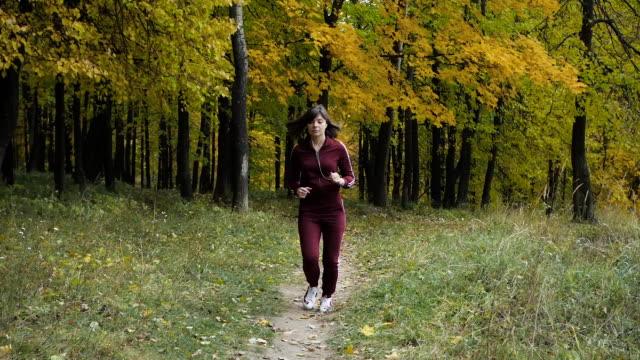 vídeos y material grabado en eventos de stock de estilo de vida saludable. chica atlética corriendo en el parque y hacer ejercicios de trotar. - sudadera