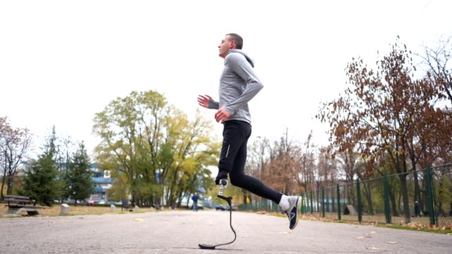 Healthy lifestyle man with a artificial leg running outdoors Young and athletic man with a artificial leg, exercising outdoors, living a healthy lifestyle recovering. artificial limb stock videos & royalty-free footage