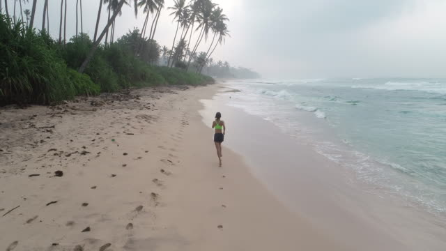 Healthy lifestyle young woman running on tropical beach during sunrise in the morning