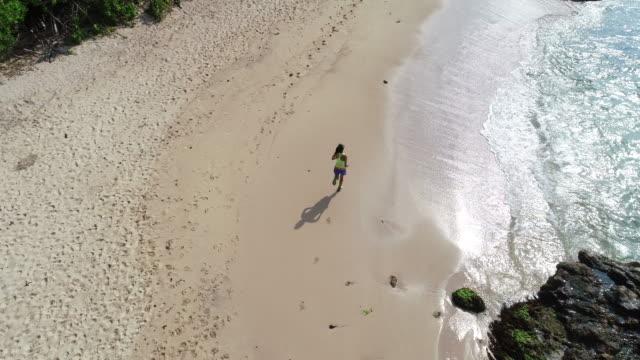 vídeos y material grabado en eventos de stock de mujer joven de estilo de vida saludable que brazos abiertos del mar en la playa, imágenes aéreas - escalada en rocas