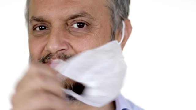 vídeos de stock e filmes b-roll de healthy man removes protective mask - remover