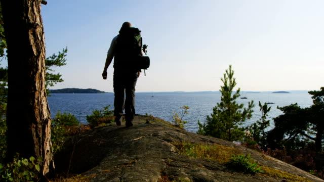 gesunder mensch mit großen rucksack spaziergänge auf dem berg am meer bei sonnenuntergang - freizeitaktivität im freien stock-videos und b-roll-filmmaterial