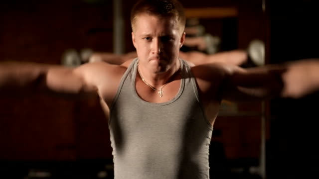 Healthy muscular young man engaged in bodybuilding video