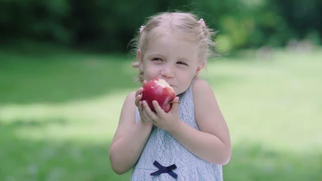 gesunde ernährung. kinder essen saftigen apfel im freien - apple stock-videos und b-roll-filmmaterial