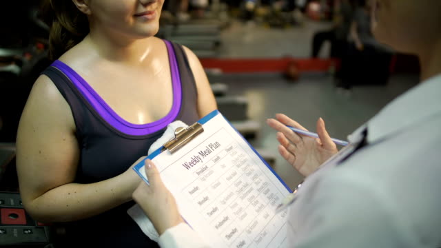 Healthy nutrition expert making weekly meal plan for client, weight loss program