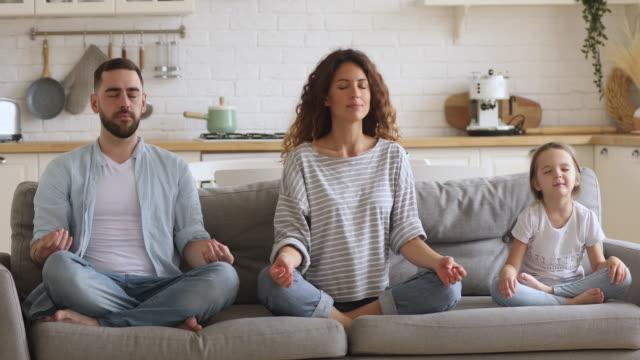 здоровые родители и дочь медитируют вместе сидеть на диване - mindfulness стоковые видео и кадры b-roll