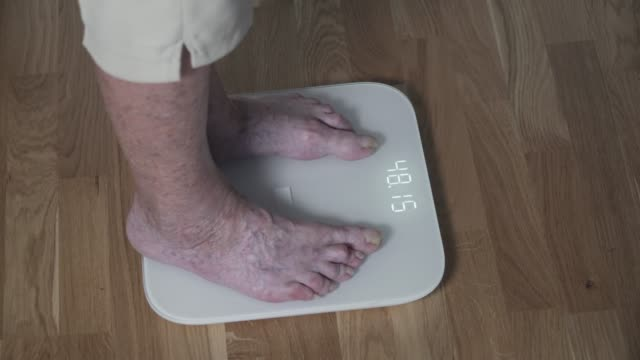 Healthy retirement lifestyle. Good weight, great physical condition, old woman. The legs bare foot of the senior female stand on the electronic weighing scales. Sore feet and crooked toes