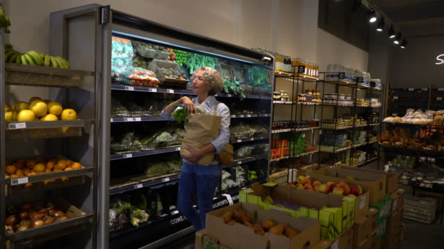 healthy senior woman shopping at an organic food store smelling the vegetables and fruits and putting them in a paper bag - замороженные продукты стоковые видео и кадры b-roll