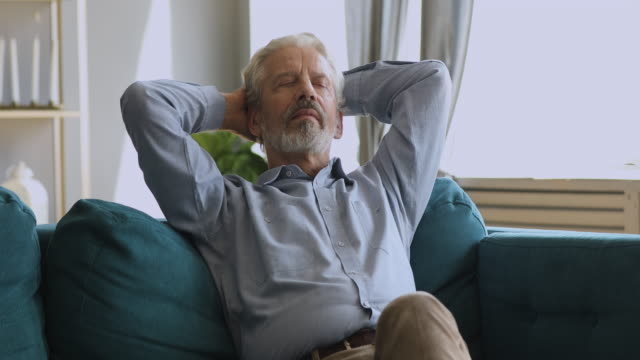 healthy serene senior man napping relaxing on couch at home - sonnecchiare video stock e b–roll