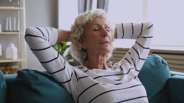 健康な穏やかなシニア女性は、新鮮な空気を呼吸ソファに休息 - 加湿器点の映像素材/bロール