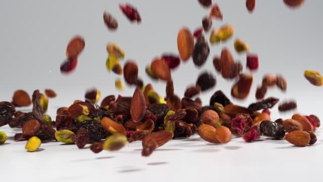 vídeos de stock e filmes b-roll de healthy trail mix falling onto a white surface in slow motion - frutos secos