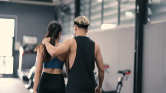 vídeos de stock e filmes b-roll de healthy two people young asian woman with man making high five gesture in gym after workout at gym couple together, teamwork and partner bodybuilding lifestyle. - gmail