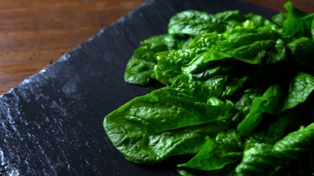 vídeos de stock, filmes e b-roll de conceito de comida vegana saudável: close-up backlight de folhas de espinafre verde recém-colhidas colocadas em uma placa de ardósia e mesa de madeira com efeito bokeh - punhado