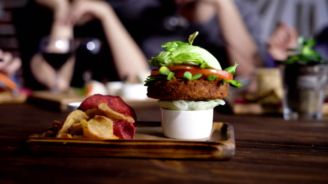 A healthy vegetable hamburger made from carrot chops, with tomato slices, lettuce leaves and soybean seedlings on onion cushion served on a wooden tray with vegetable chips and sauce video