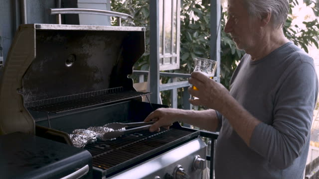 healthy vibrant senior citizen man holding a beer and cooking on a bbq - aluminum foil stock videos & royalty-free footage