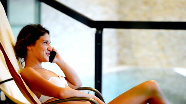 Healthy woman resting in spa and talking on cell phone video