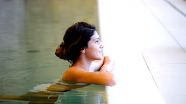 Saine femme nager dans la piscine et vous détendra avec bain à remous - Vidéo