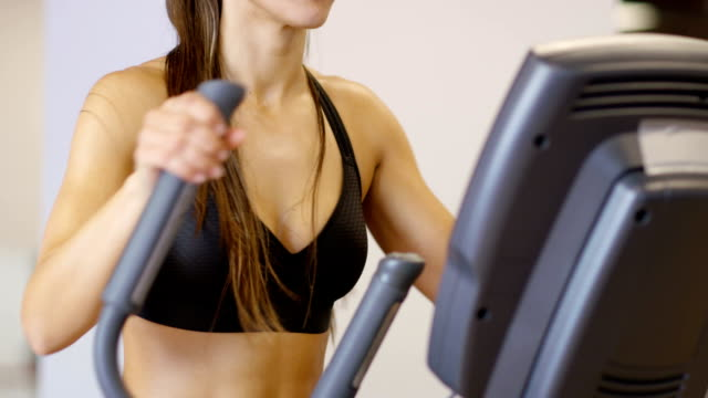 Healthy woman training on ellipse exercise machine in fitness gym video