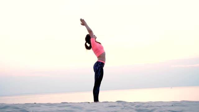 Healthy, young beautiful woman meditating, practicing yoga among the sand, on the beach, by the sea, river, at dawn, at sunrise, closeup video