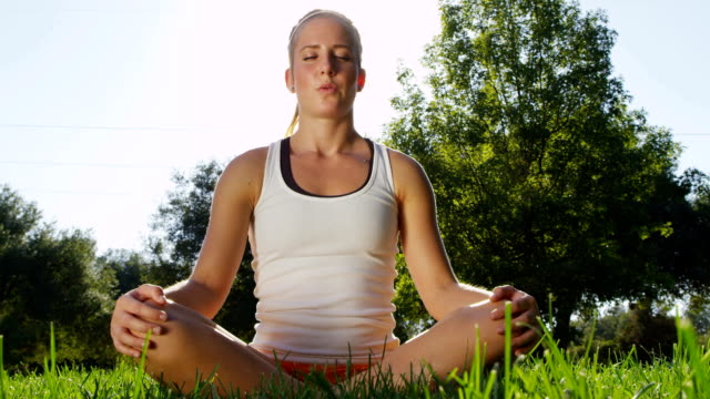 Healthy young woman relaxing in park video