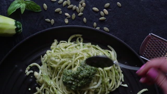 """Healthy Zucchini Noodles with Pesto """"Spaghetti"""" noodles made out of Zucchini is called """"Zoodles"""", a fad amongst healthy eaters. This dish is served up with pesto and a sprinkle of italian parmigiano reggiano. pesto sauce stock videos & royalty-free footage"""