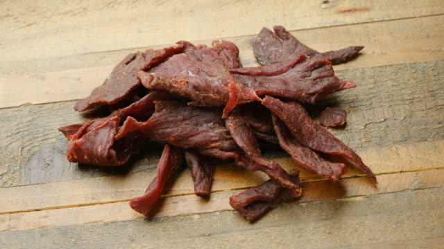 Heap of Beef jerky close up Heap of Beef jerky close up over a wooden table jerky stock videos & royalty-free footage