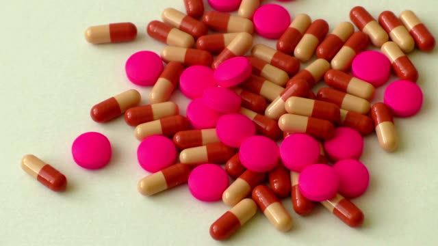 Heap of colorful pills on a white background video