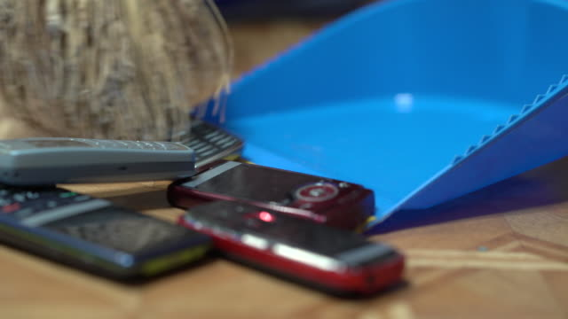 heap of old mobile phones on dustpan - obsoleto video stock e b–roll