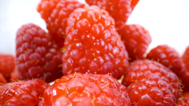 A heap of red raspberry fruit on the basket