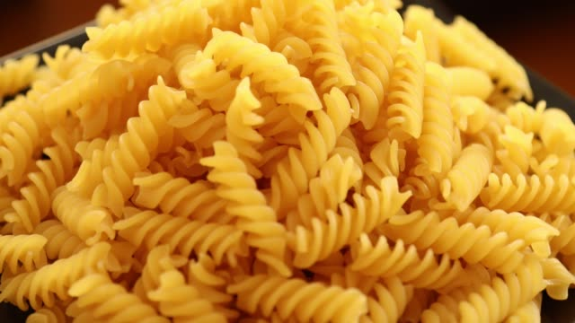 Heap of rotating fusilli pasta on plate closeup 10 Heap of rotating fusilli pasta on plate closeup uncooked pasta stock videos & royalty-free footage