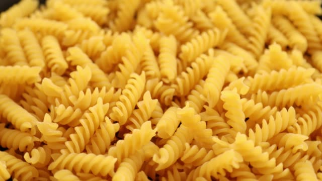 Heap of rotating fusilli pasta on plate closeup 2 Heap of rotating fusilli pasta on plate closeup uncooked pasta stock videos & royalty-free footage