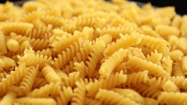 Heap of rotating fusilli pasta on plate closeup 5 Heap of rotating fusilli pasta on plate closeup uncooked pasta stock videos & royalty-free footage