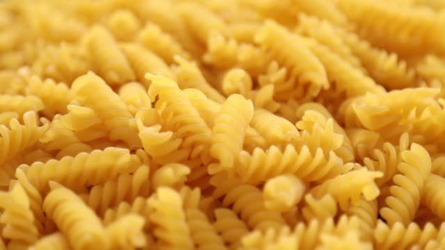 Heap of rotating fusilli pasta on plate closeup 6 Heap of rotating fusilli pasta on plate closeup uncooked pasta stock videos & royalty-free footage