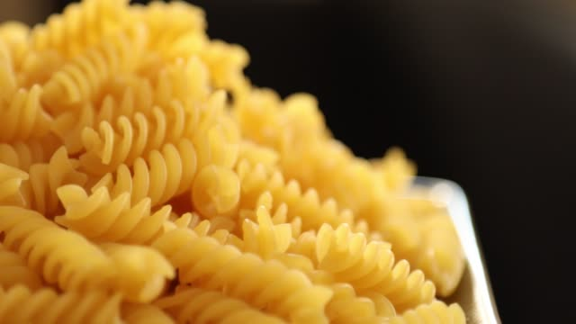 Heap of rotating fusilli pasta on plate closeup 9 Heap of rotating fusilli pasta on plate closeup uncooked pasta stock videos & royalty-free footage