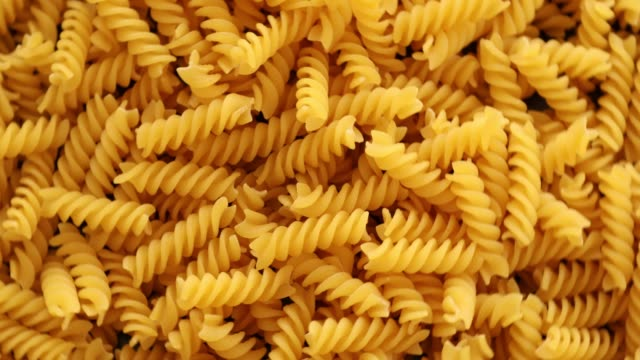 Heap of rotating fusilli pasta on plate closeup Heap of rotating fusilli pasta on plate closeup uncooked pasta stock videos & royalty-free footage