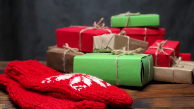 Heap of rustic gift boxes Stack of gift boxes and red mittens on rustic wooden surface. Red, brown and green colors. Dolly shot heap stock videos & royalty-free footage