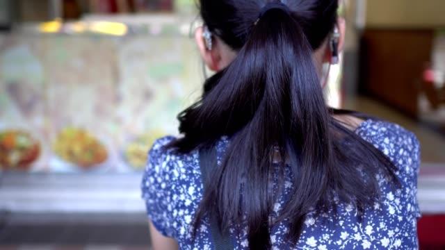 vídeos de stock, filmes e b-roll de a criança da perda da audição está esperando por um pãezinhos fora da porta chinesa do restaurante. com as costas para a câmara. - surdo