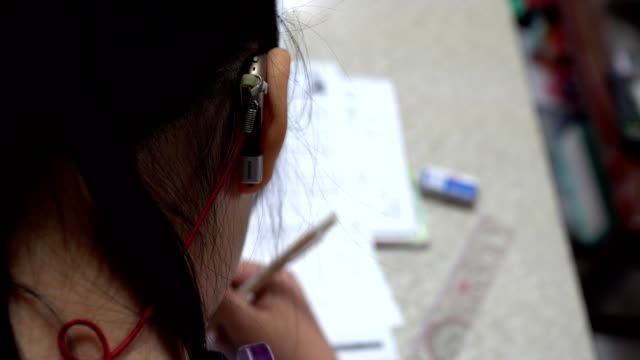 Hearing loss girl doing homework. Focus is on the little girl's ear. The subject is on the left. Images are about education, development, effort, and hearing loss. disability stock videos & royalty-free footage