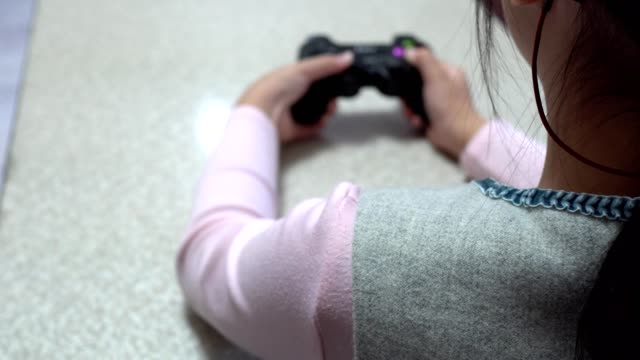 hearing loss girl playing video games with joystick. focus is on little girl's shoulder. - kids holding hands filmów i materiałów b-roll