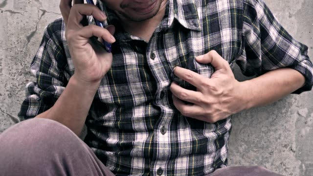 vídeos de stock e filmes b-roll de 4k video: heart attack concept, a man clutching his chest while using phone to emergency calling. - coração fraco