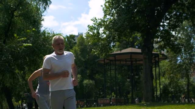 vídeos de stock e filmes b-roll de heart attack while jogging, old person has health problems, suffering chest pain - ataque cardíaco